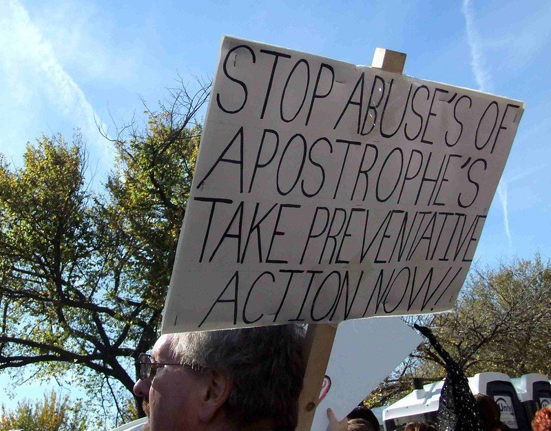 "Protester with sign which reads - ""Stop abuse's of apostrophe's take preventative action now!"""