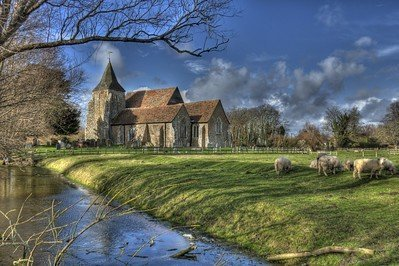 Rural Chruch with sheep and stream in foreground.