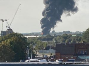 A large column of black smoke arises in the distance.